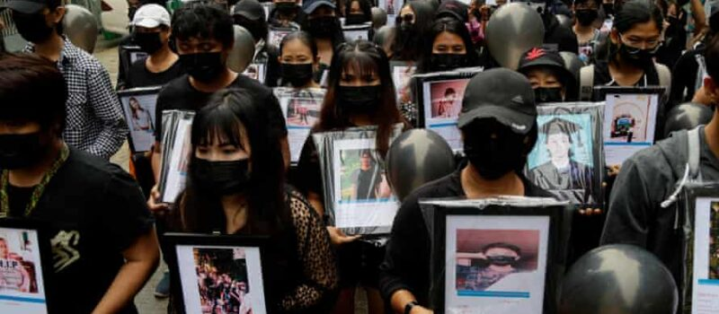 Myanmar demonstrators wearing black hold black balloons and pictures of the people shot dead by troops during a protest in Yangon on 5 April.